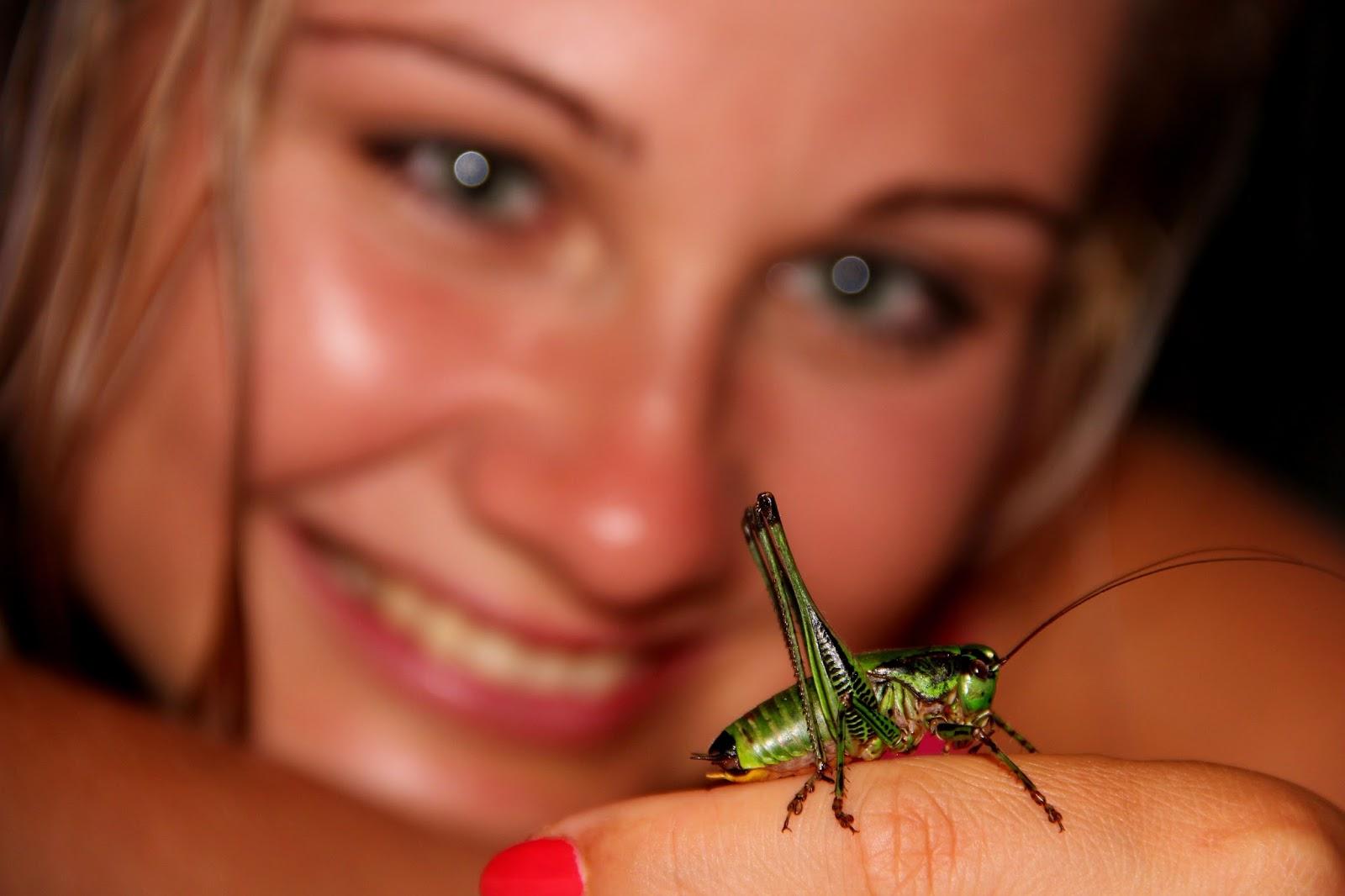 A lady holding a grasshopper.