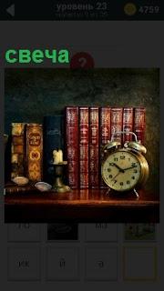 На полке с книгами стоит будильник и потухшая свеча, хозяин вышел на работу закончив свои дела