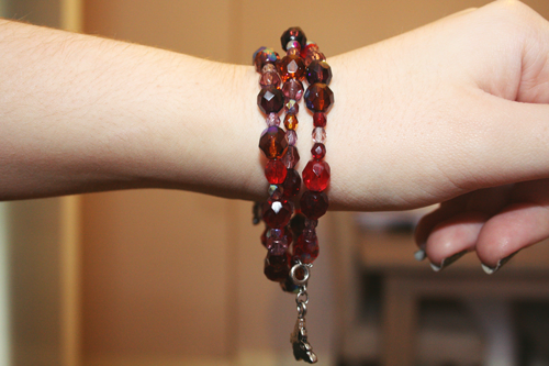 a girl's arm with a red beaded bracelet