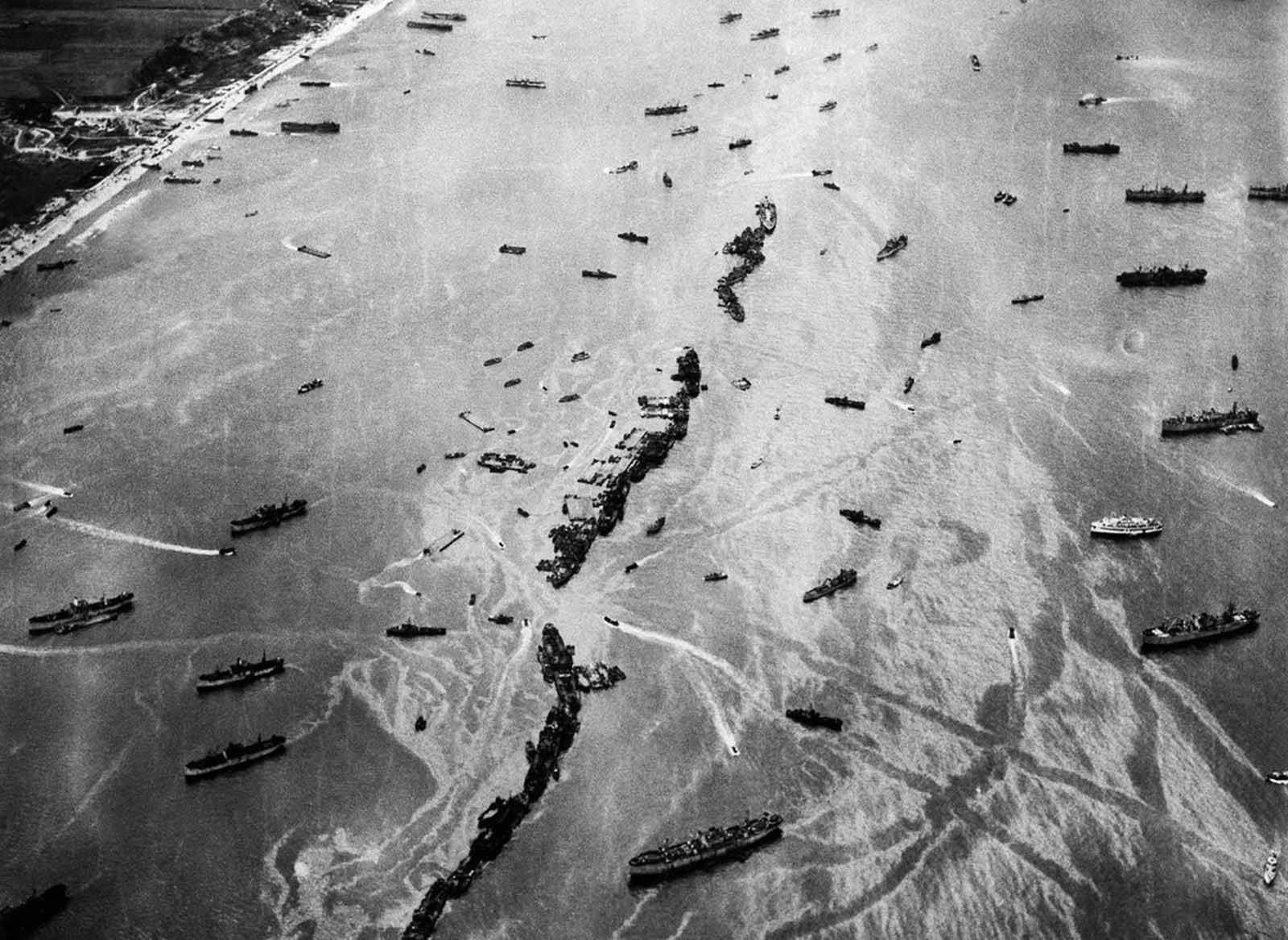Thirteen liberty ships, deliberately scuttled to form a breakwater for invasion vessels landing on the Normandy beachhead lie in line off the beach, shielding the ships in shore. The artificial harbor installation was prefabricated and towed across the Channel in 1944.