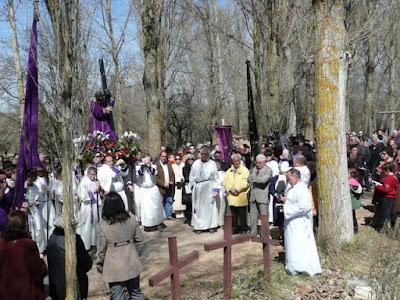 Imagen del viacrucis: Jesús llevando la cruz, cofrades vestidos de blanco, público y tres cruces en primer plano.