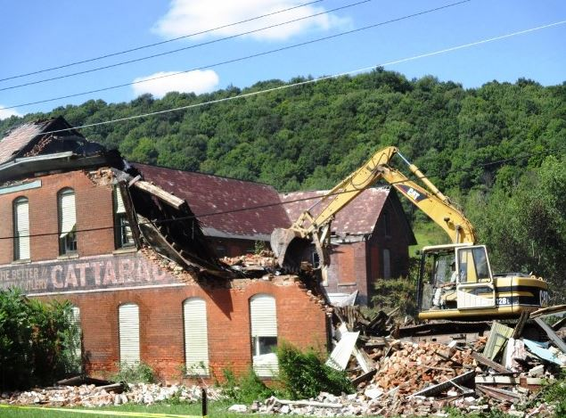 partially destroyed facade of south building, Cattaraugus Cutlery factory with machinery chewing away at remainder