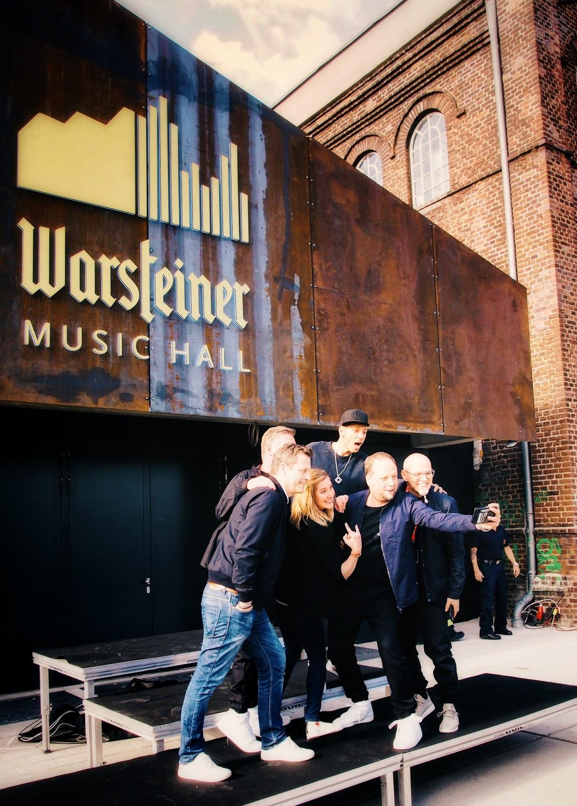 Atomlabor Blog on Tour in der Warsteiner Music Hall in Dortmund - Die Fantastischen Vier mit Catharina Cramer und Alexander Richter vor dem Eingang der Halle auf einem Podest beim Selfie