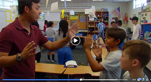 snapshot of video profile, shot of Lennon working with students in a busy classroom