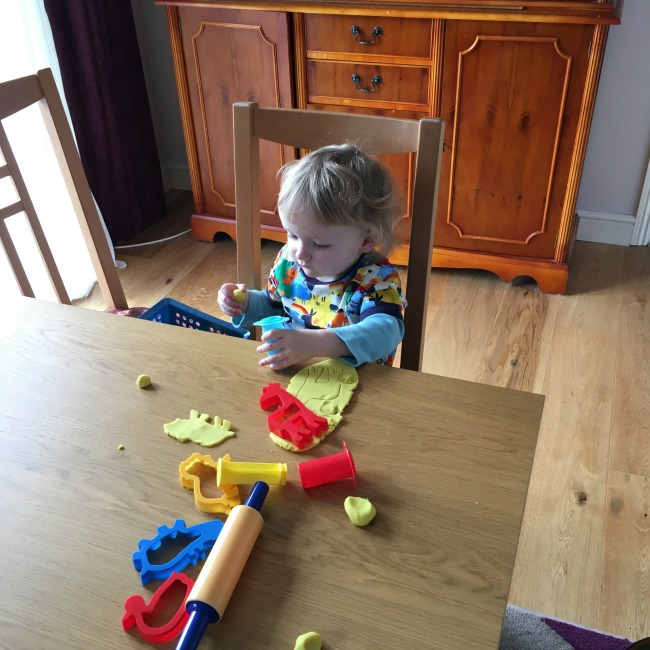 toddler sat at table playing with play dough