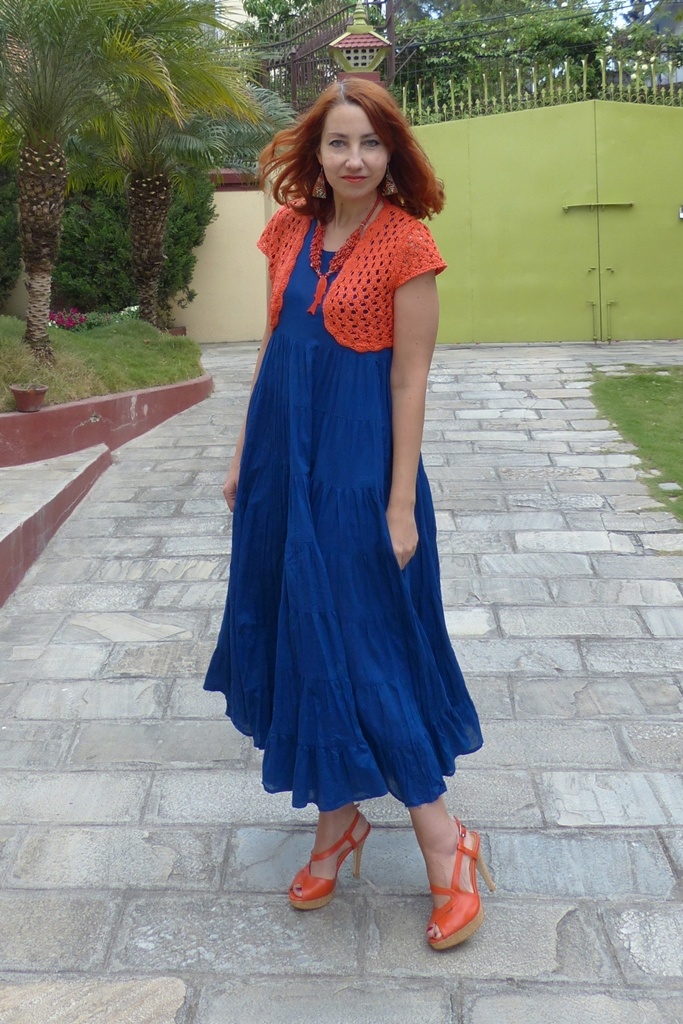 Orange shrug worn over blue maxi dress