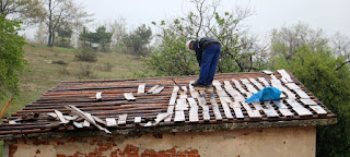 Bekir working on the roof in the cold rain