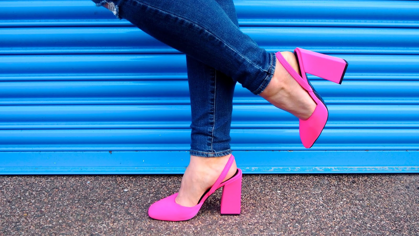 ASOS Design Neon Pink Block Heeled Slingback shoes with jeans in front of a blue wall