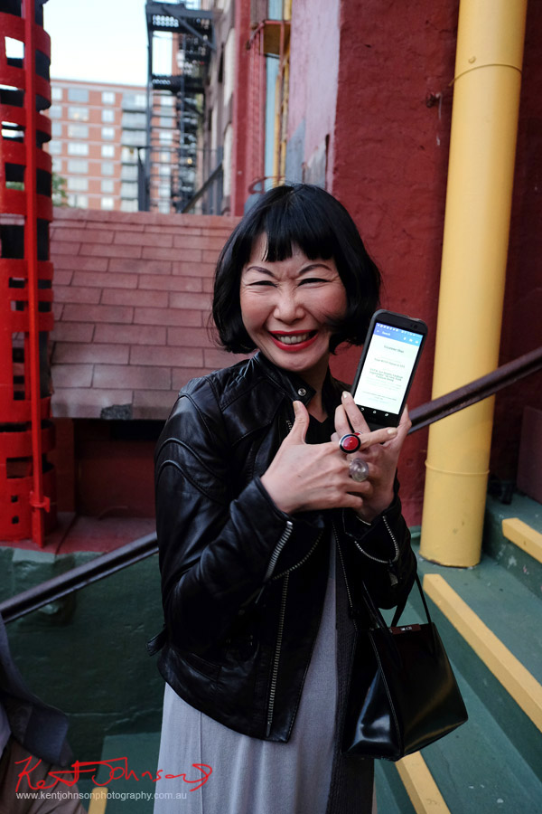 A happy fashionista shows their digital ticket on their phone. Street Fashion Sydney - New York Edition photographed by Kent Johnson