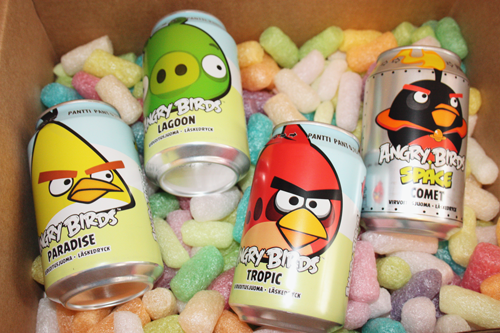 a selection of angry birds sodas in a variety of flavours, lying on a bed spread with packaging peanuts