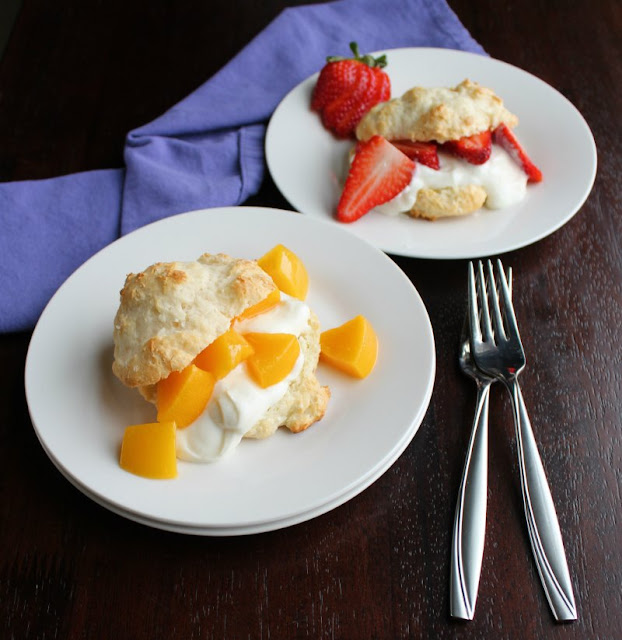 two plates, one with a peach brunch shortcake and one with sliced strawberries and yogurt in a biscuit