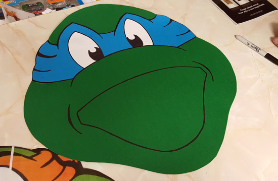 The green card was used to cut out the shape of the teenage mutant ninja turtles.  We tried to keep the same shape and style of the party bags.  We then used the blue for mask and the white for the eyes.  The sharpie was used to fill in the detail of the face and left to dry out.