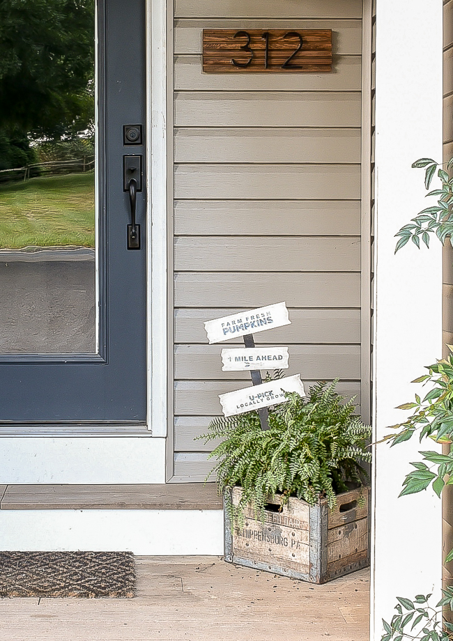 Front porch with updated Dollar Tree yard sign.