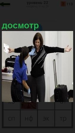 Производится досмотр охраной женщины в помещении