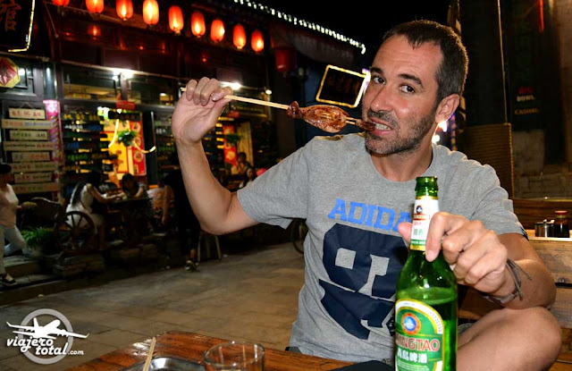 Comida china - brocheta de calamar y cerveza Tsingtao