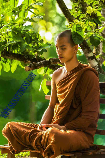 A buddhist tibetian monk doing meditation in Dhyan Mudra or Hand gesture for meditation, on bench in garden or park