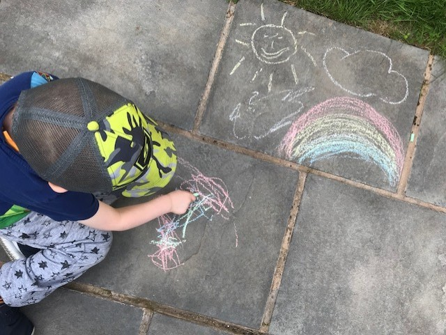 Little boy drawing with chalk on a patio, with a sun, rainbow and cloud drawn on the slab next to him