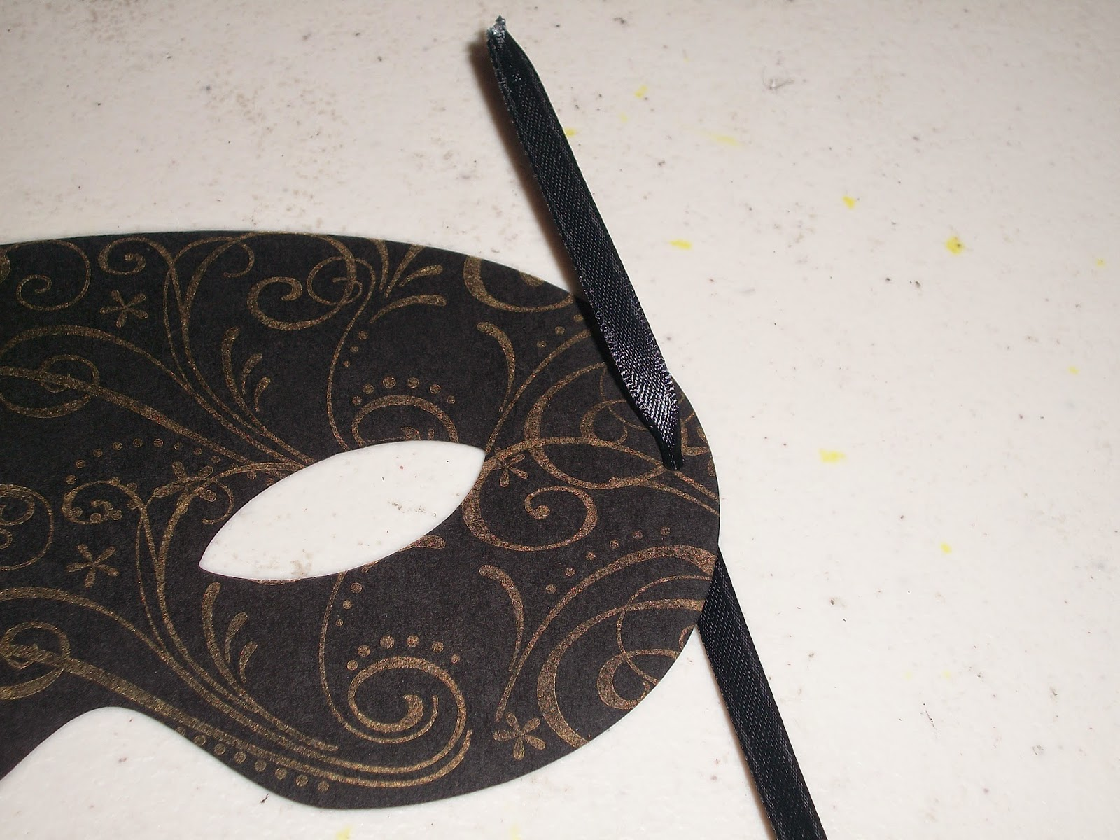 Punch a tiny hole on each side of mask and add ribbon