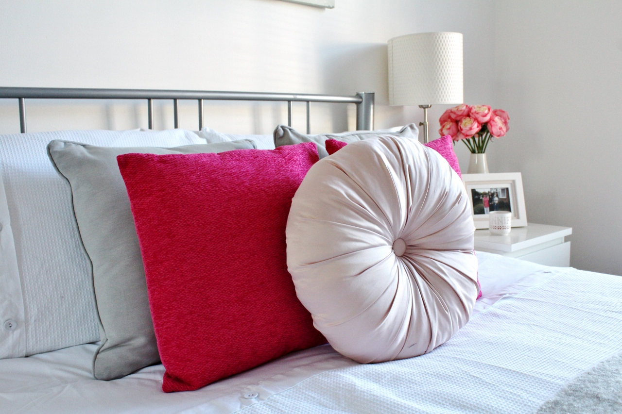 Pink and grey cushions on bed