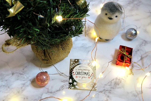 a mini christmas tree next to a toy penguin and lights