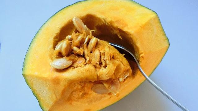 スプーンでかぼちゃのワタや種を取り除く