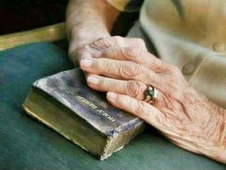 mãos idosas seguram Bíblia Sagrada sobre as pernas.