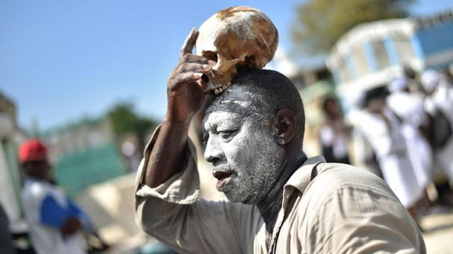 A voodoo devotee with a skull on top of his head is seen during ceremonies honoring the Haitian voodoo spirit of Baron Samdi and Gede on the Day of the Dead in the Cemetery of Cite Soleil, in Port-au-Prince, Haiti on November 1, 2017 CREDIT: AFP.