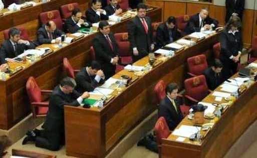 Senadores paraguayos orando de rodillas