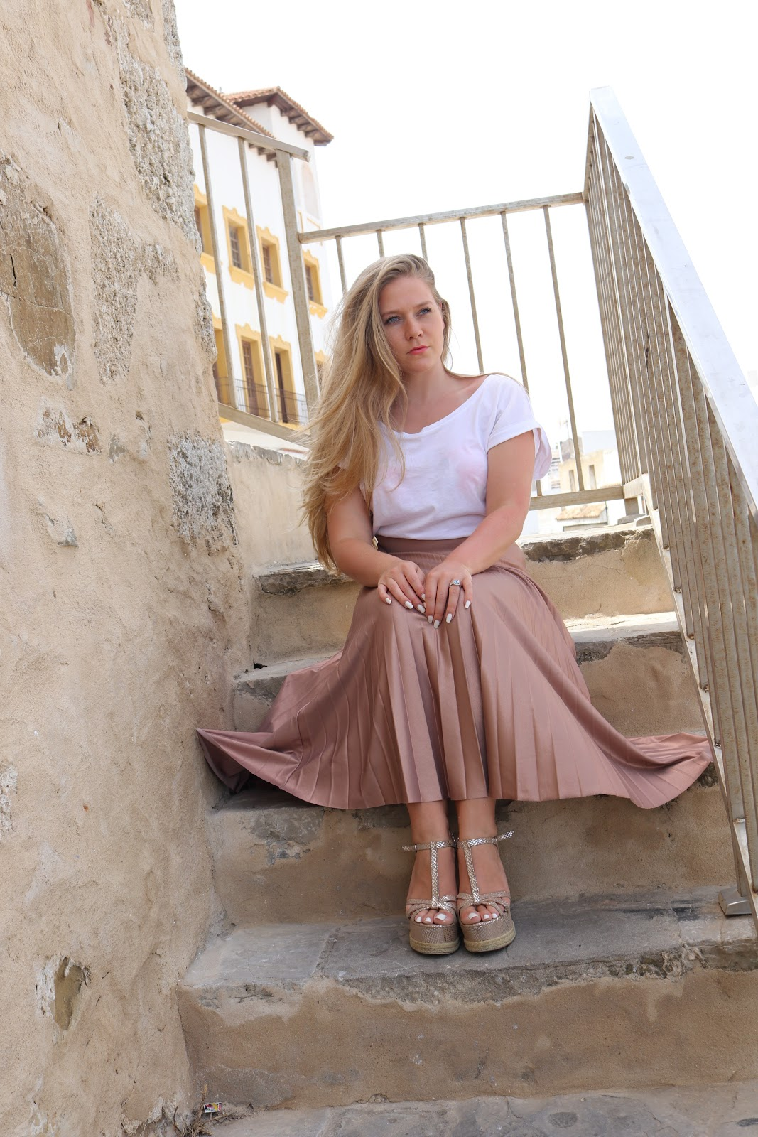 Blonde girl wearing metallic skirt sitting on stairs in Tarifa, Spain