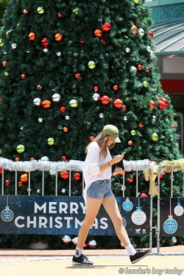 Lucy Keighley, Hastings, on her cellphone, mobile phone, walking through the Hastings CBD, Hastings, past the Christmas tree, in pleasantly hot sunny weather. photograph
