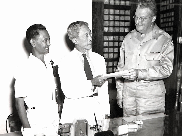 Colonel William Bloy (unsure), CO, Base R, presents check to Governor Modesto Castillo and Mayor Gregorio Areglado for property damage at Batangas, P.I. Taken 2 April 1947.