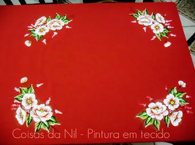 toalha de mesa de oxford vermelho com papoulas brancas pintadas nos cantos