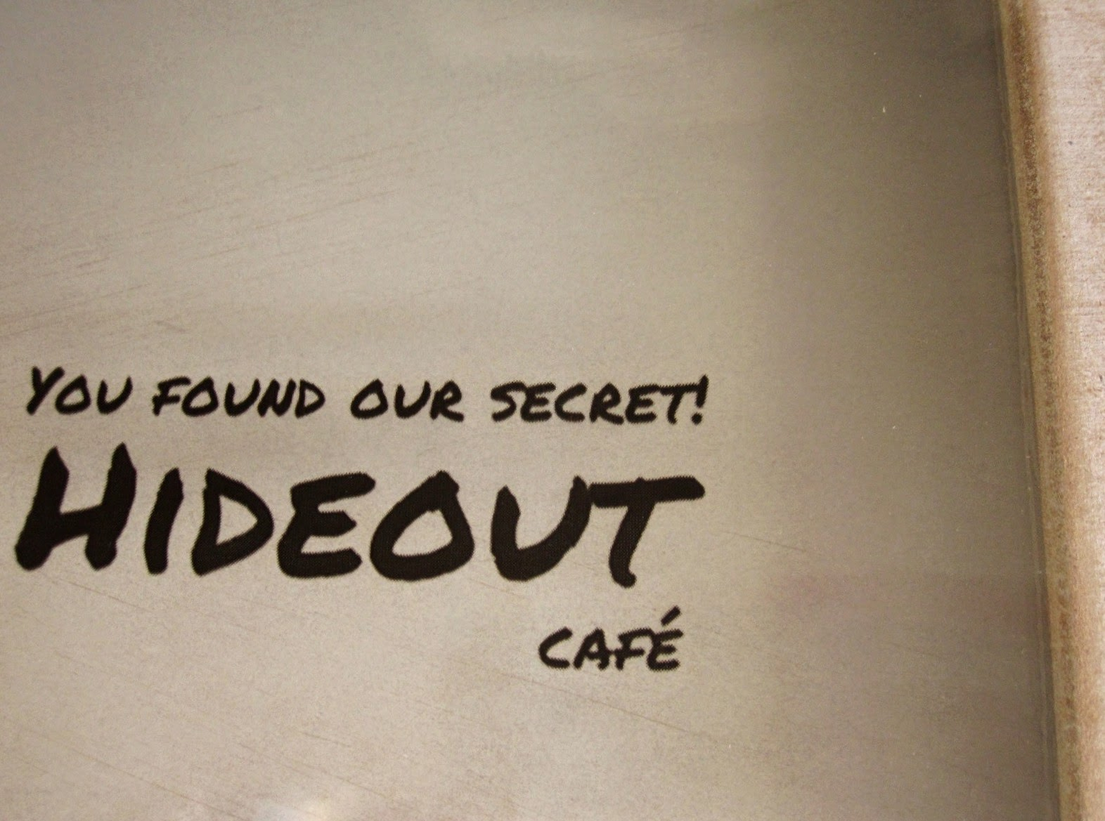 Modern dolls' house miniature window sign which says 'You've found our secret! Hideout cafe""