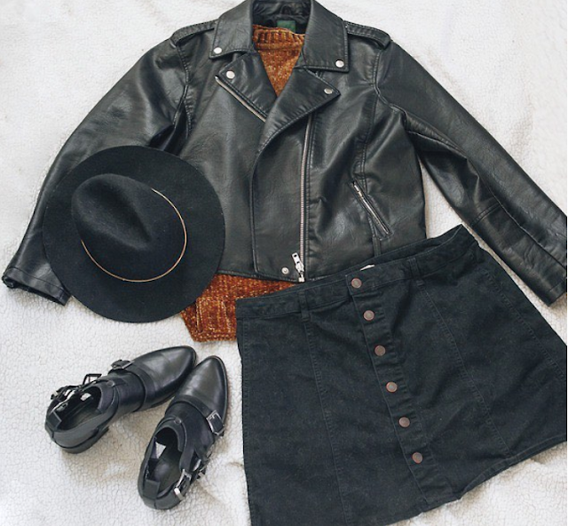 A flatlay of a black faux leather moto jacket over an ochre colored sweater, a black button down skirt, a black wide brim hat with a gold accent and black boots with three buckles.