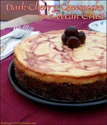 Dark Cherry Cheesecake in a Pecan Crust starts with a pecan crust as a great compliment to this classic cheesecake swirled with syrup, then topped with dark sweet cherries. | Recipe developed by www.BakingInATornado.com | #recipe #dessert