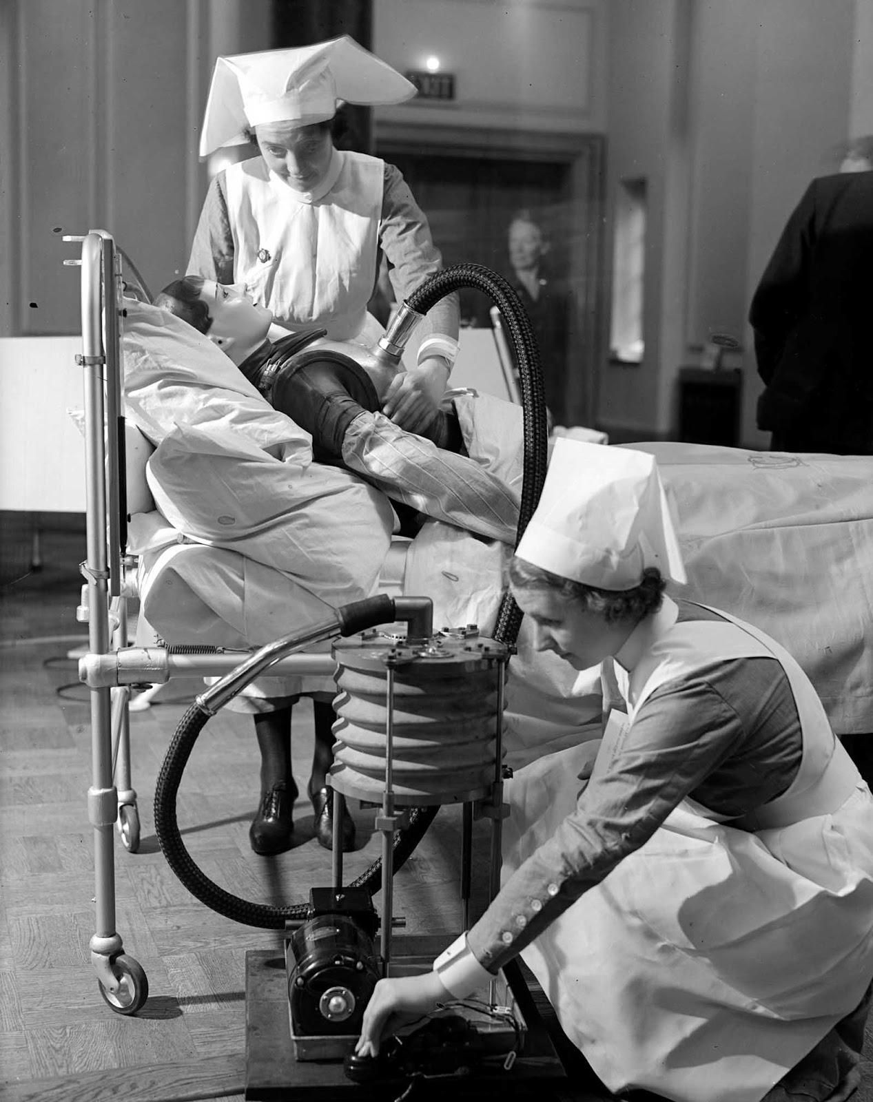Las enfermeras practican operar una chaqueta respiratoria que realiza una función similar a un pulmón de hierro, alrededor de 1938.