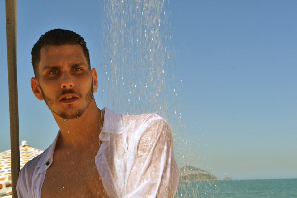 Lucas Monteiro, candidato a Mister Caxias 2017, toma banho de chuveirinho durante ensaio em praia do Rio. Foto: Sidney Boock