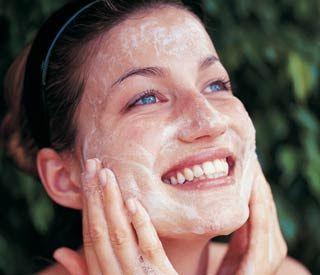 Cuidados de la piel. Mujer aplicándose crema en el rostro