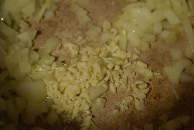 Minced garlic being added to the pot.