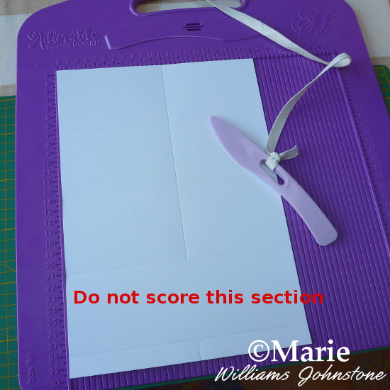 Scoring a sheet of card on a craft scoreboard to make handmade pop up box cards