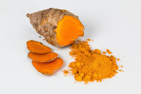 An image in which a piece of dried turmeric alongwith turmeric powder is shown