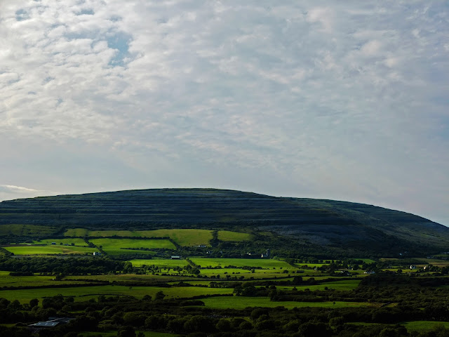 Sunlight on a hill of green fields in the Burren, Co.Clare.