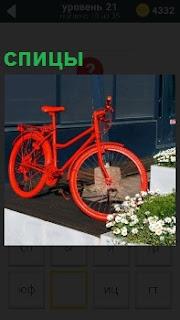 Около дома стоит велосипед красного цвета с исправными спицами на коврике рядом с цветущей клумбой
