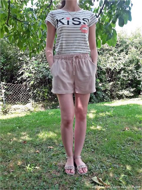 T-shirt w paski, jasnoróżowe materiałowe krótkie spodenki, beżowe sandały w etniczne wzory