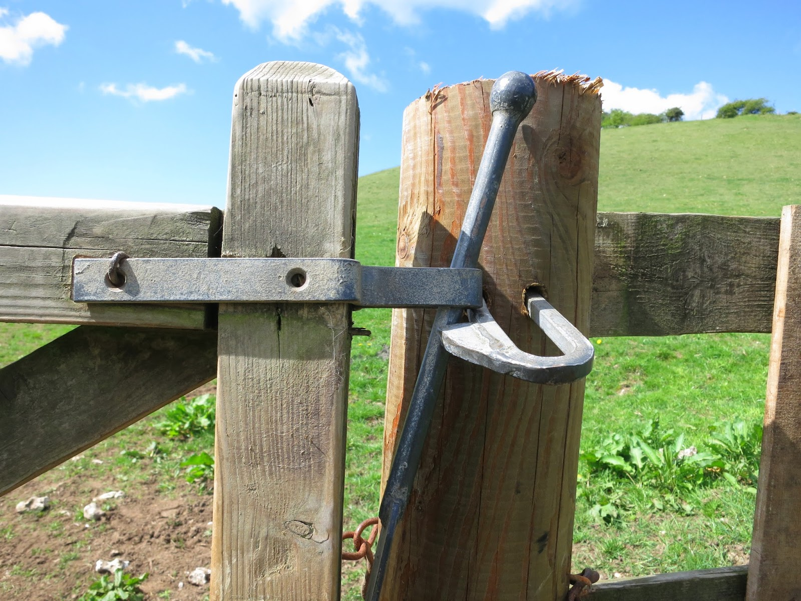Wooden field gate with metal opening bar and link chain.