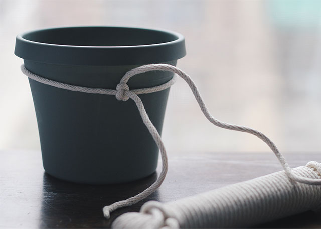 Create a hanging planter using clothesline cord and a plastic planter