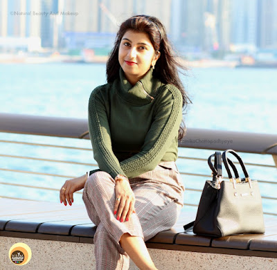 Anamika Chattopadhyaya sitting at Avenue of Stars, Tsim Sha Tsui Promenade, Hong Kong along the harbor