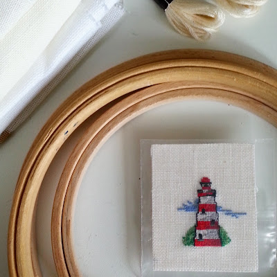 Miniature cross stitch picture of a light house, in the middle of a set of embroidery hoops, next to two skeins of embriodery thread and a pile of cross-stitch fabric.