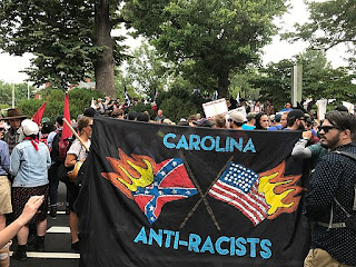 "Banner reads ""Carolina Anti-Racists"" and shows burning Confederate battle flag and burning U.S. flag."