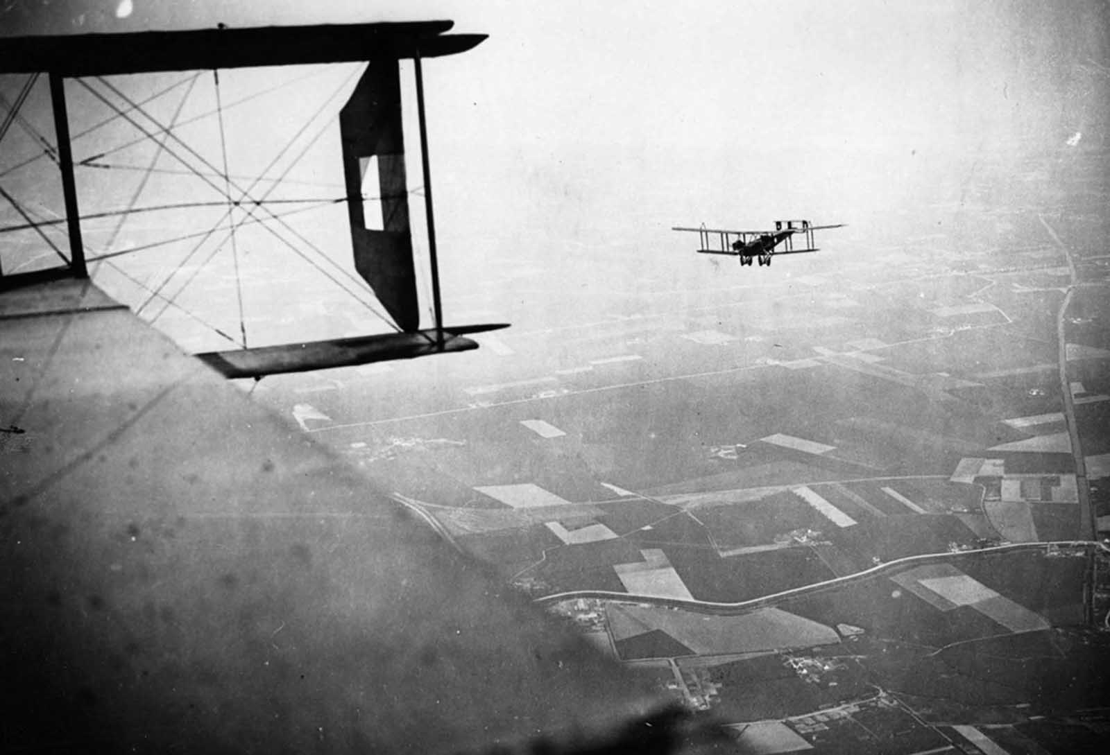 British Handley-Page bombers on a mission, Western Front, during World War I. This photograph, which appears to have been taken from the cabin of a Handley-Page bomber, is attributed to Tom Aitken. It shows another Handley-Page bomber setting out on a bombing mission. The model 0/400 bomber, which was introduced in 1918, could carry 2,000 lbs (907 kilos) of bombs and could be fitted with four Lewis machine-guns.